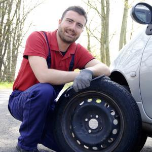 Man in red shirt repairing a car tyre with breakdown assistance.